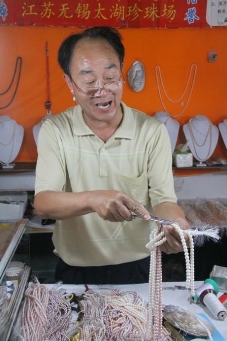 图为陈金木先生在为顾客讲解如何鉴别珍珠的真伪,陈先生是