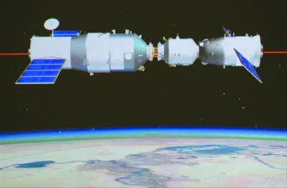 大屏幕上拍摄的神舟九号与天宫一号手控交会对接成功的画面(2012