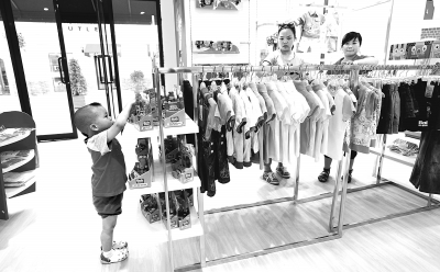 童装专柜里,家长领着孩子在选购童装。