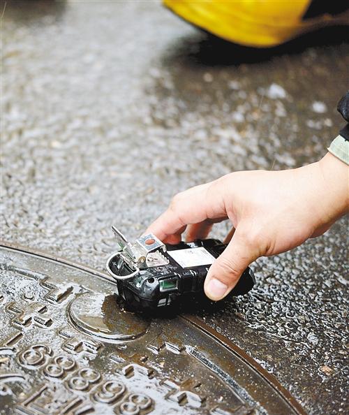 消防队员对一处井盖测试口进行检测