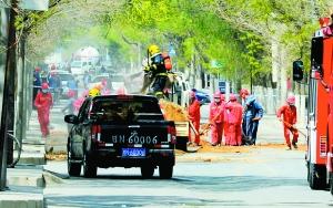 应急处置队伍对溢洒的液态甲醛进行彻底清理。本报首席记者 裴强 摄警戒线外的市民戴口罩捂住口鼻。
