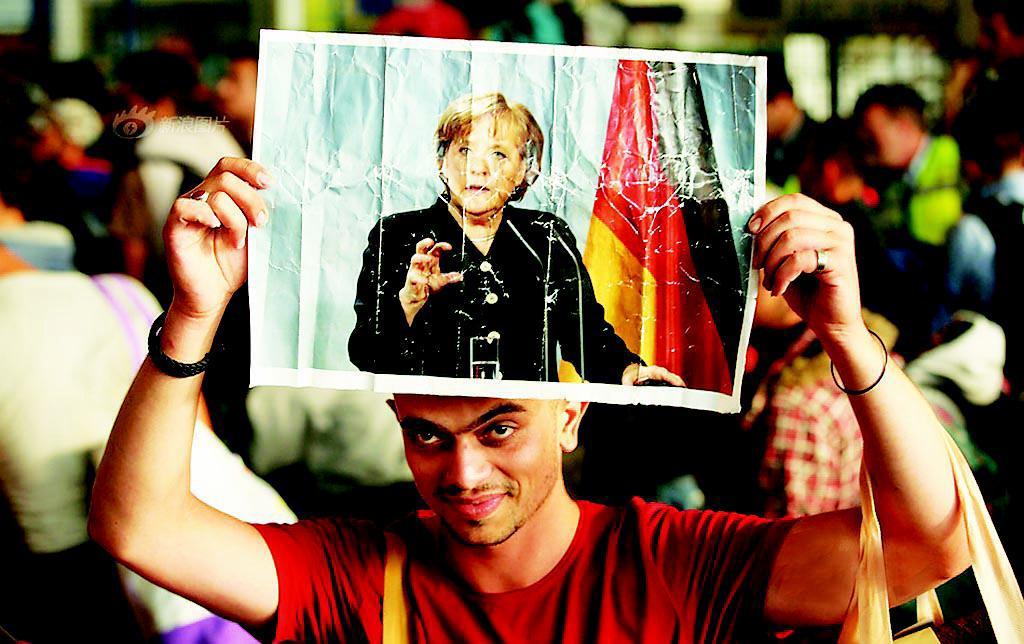 高举默克尔照片 上万难民入德